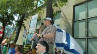 ITW founder Mark Vandermaas speaks at anti-Al Quds Day rally, Toronto in 2015 beside supporter holding ITW 'ASK ME ABOUT ISRAEL'S LAND TITLE DEED' poster.